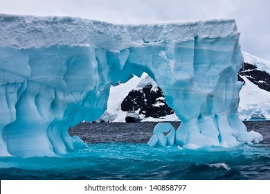 Huge blue iceberg with cruise ship in the distance, Antarctica