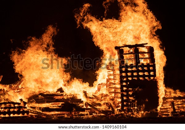 Huge Bonfire With tall flames and smoldering embers, wooden logs and pallets.
