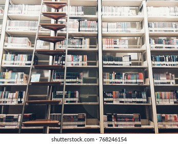 A huge bookshelf with a ladder for climbing to get entertainment and knowledge (also called edutainment) in a library that is a collaboration between private and public sector.