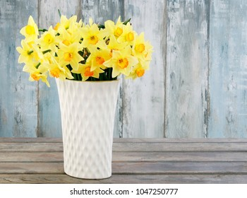 Huge bouquet of yellow daffodils on blue wooden background.