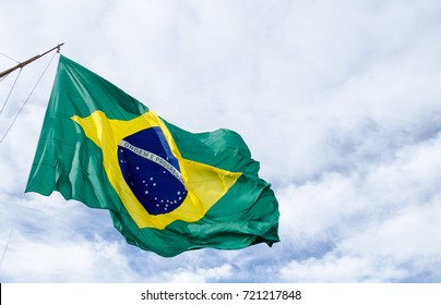a huge Brazilian flag flying on a sailboat on a blue cloudy sky background