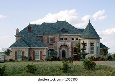Huge brick modern French provencial style house with ornate fountain and beautiful landscaping on small lake.