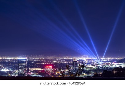 Huge bright powerful spotlight rays over the night sky panorama of Los Angeles city from Hollywood Hills.