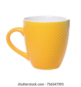 A huge bright yellow faience mug, with decorative pimples on a white background.