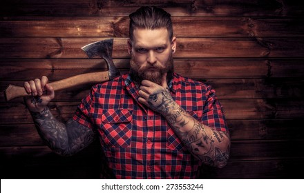 Huge brutal man with beard and tattooes holding axe