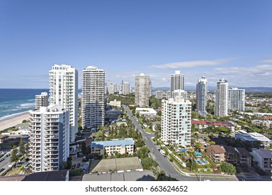 Huge buildings in modern city near sea, sky is blue and has white clouds, natural look with green trees, roads are full with vehicles.