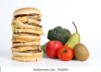 A huge burger next to fruit and vegetables