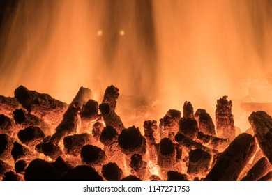 Huge burning bonfire with dimly eyes at night. A pyre with burning wood, flames and luminous dots like unreal eyes. Heat of burning wooden logs.