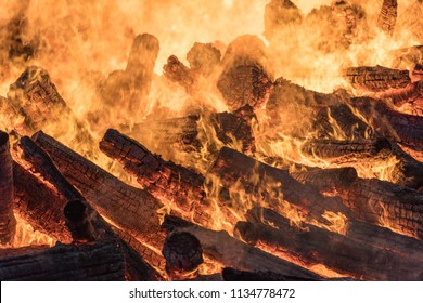 Huge burning bonfire at night. A pyre with burning wood and flames. Heat of burning wooden logs.