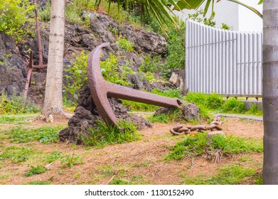 Huge cast iron boat anchor with chain against a block of stone in a town in Tenerife