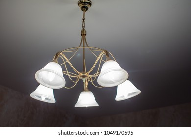 Huge chandelier closeup with electric bulbs on fancy ceiling