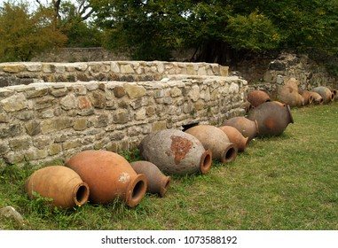 Huge clay jugs kvevri for making wine  in Georgia against the backdrop of a stone wall and green grass
