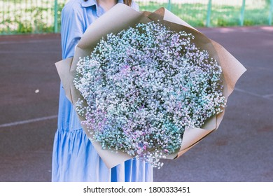 Huge colorful bouquet of gypsophila, bunch of flowers in hands, girl in blue dress with flowers