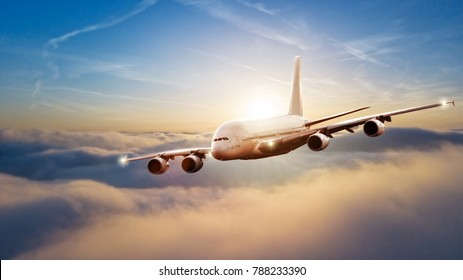 Huge commercial airplane flying above clouds in beautiful sunset light. Travel and business concept