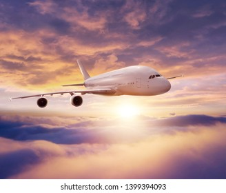 Huge commercial airplane flying over dramatic sunset sky. Jet plane is the fastest mode of modern transportation.