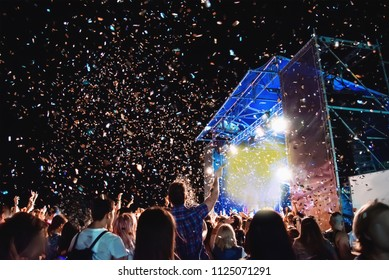 Huge concert crowd at night under the open sky on the roof. Pyrotechnic salute fireworks from multicolored red, blue and yellow confetti. Silhouettes of people having fun.