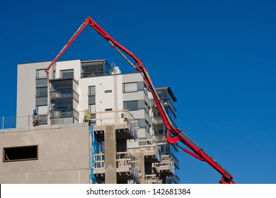 Huge concrete pump with tall arm pumping conrete on top of the building with unrecognizeable workes