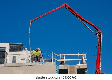 Huge concrete pump with tall arm pumping concrete on top of the building with workes