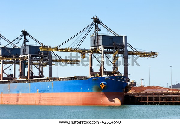 Huge cranes unloading ore from a bulk carrier