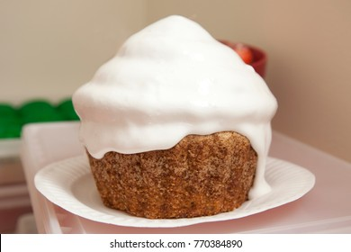 a huge cream cheese icing covered carrot cake cupcake