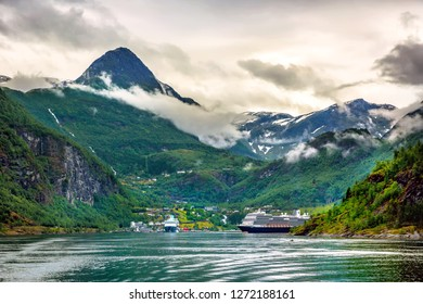 Huge cruiser in the middle of the fjords with high peak mountain in Norway