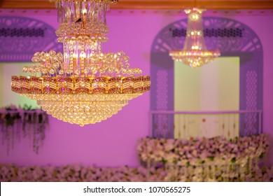 Huge crystal glass chandeliers hanging on ballroom. Crystal chandelier hanging on the ceiling.