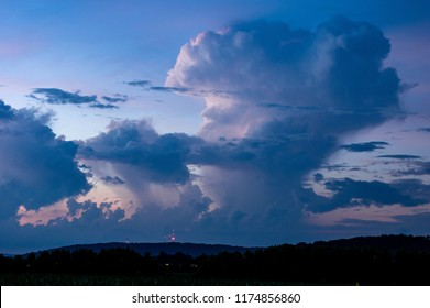 Huge cumulonimbus clouds at blue hour reflecting some of the last glows of the set sun.