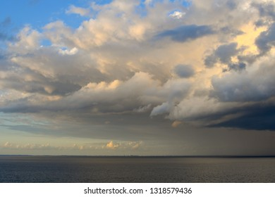 A huge, dark storm cloud with rain approaches at sunset near the visible coastline with structures on the coast of Denmark on the Baltic sea