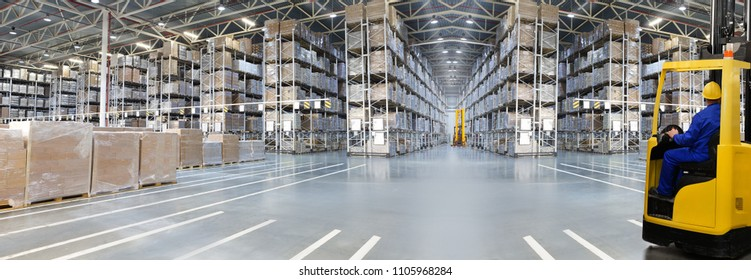 Huge distribution warehouse with high shelves and loaders. Bottom view.