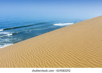 Huge dunes of the desert. Sea surf against sand.