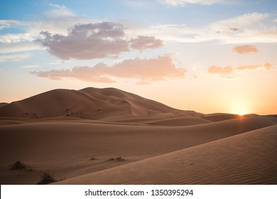 Huge dunes in the Sahara desert with a beautiful sunset in the background under a cloudy sky in Erg Chebbi, Morocco