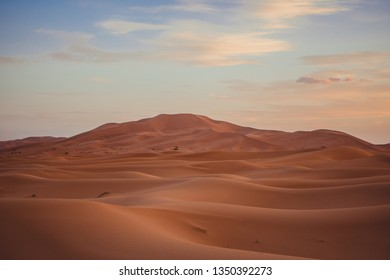 Huge dunes in the Sahara desert under a blue sky with some clouds, in Morocco