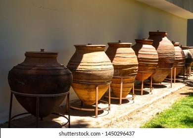Huge earthenware jugs exhibited in the sun outside. Old pottery pots outside. Old orange clay jugs.