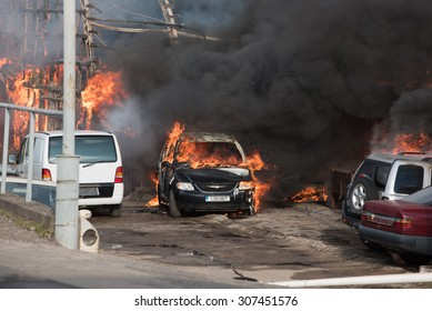 Huge fire of industrial buildings and cars. Open fire and black smoke.