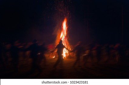 Huge fire at night and young people around. Pagan festival of Walpurgis night: bonfires, dancing wildly, demons, witches. Folk festival, popular holiday. German legends, St. Walburgas, Satanism, devil