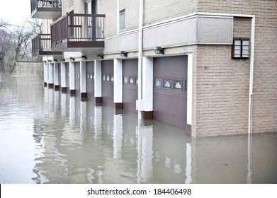 A huge flood near an apartment with many brown garages on a cloudy day.