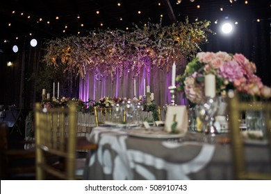Huge flower garland hangs over a restaurant table prepared for a wedding couple