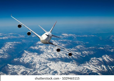 Huge four engines airplane flying over the Alps