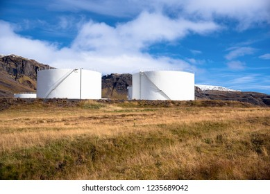 Huge Fuel Tanks under Blue Sky with Mountains in Background and a Grassy Field in Foreground.