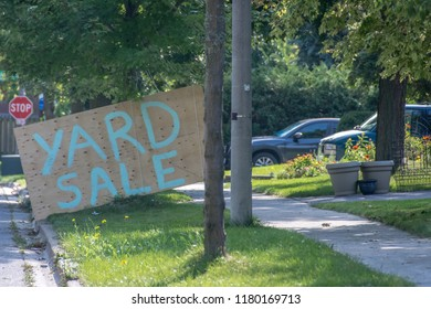 A huge garage sale sign painted on a 4 x 8 piece of plywood, with a stop sign in the background, between the side of the road and the sidewalk in a suburban neighborhood.