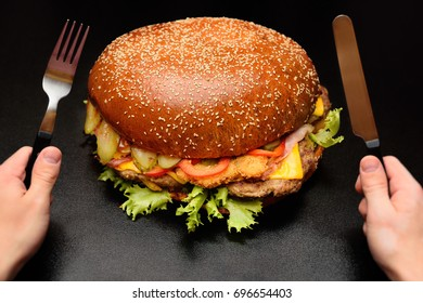 Huge giant big burger on a dark background close-up