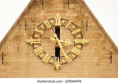 Huge golden clock on the facade of a building. Architectural detail