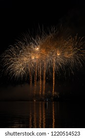 Huge golden rain in fireworks over Brno's Dam with lake reflection