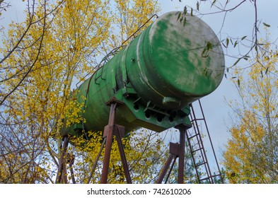 Huge green aluminium barrel on rusty metal support used as water tower near Grabovka village, Gomel region, Belarus, with a autumn trees with yellow falling leaves and foggy blue sky.
