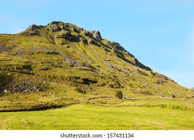 A Huge Green Hill With Grass on It