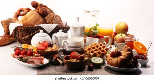 Huge healthy breakfast on table with coffee, orange juice, fruits, waffles and croissants. Cereals and balanced died. Good morning concept.