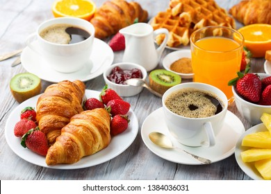 Huge healthy breakfast on white wooden table with coffee, orange juice, fruits, waffles and croissants. Selective focus. Good morning concept.