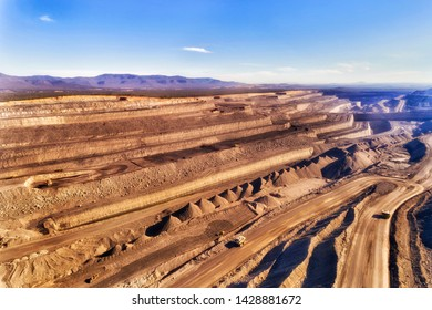 Huge heavy trucks carrying raw minerals of black coal from the bottom of open cut coal mine in Upper Hunter Valley Liddell area, Australia. Elevated aerial view across depth of the mine.