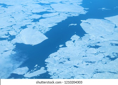 Huge ice floes on the sea. Ice drift. Top view from the window of the plane. Background. Landscape.