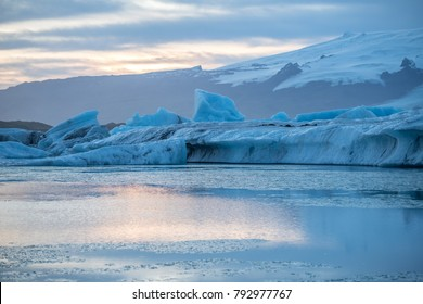 Huge iceberg in Jokulsarlon, glacier in Iceland with sunset and red sky